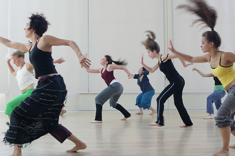 Students dance in a studio during a class.
