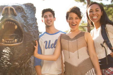 Three students smile for a photo with The Bruin statue.