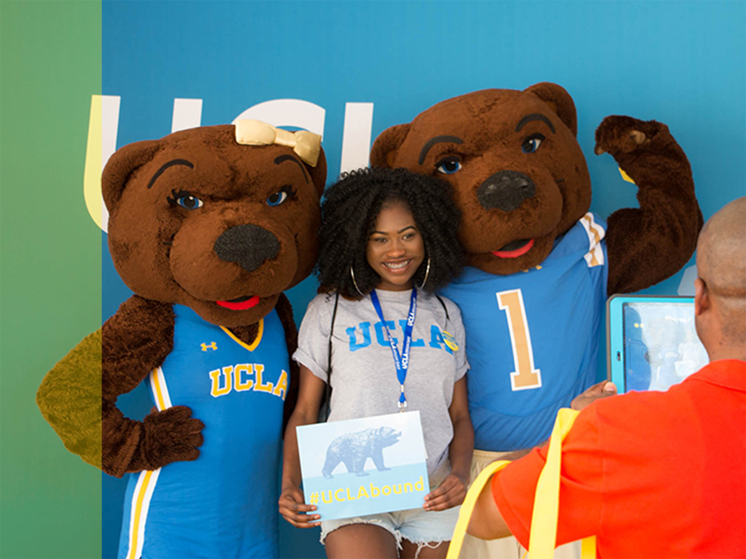 A female student holding a #UCLAbound sign poses with Joe and Josie Bruin.