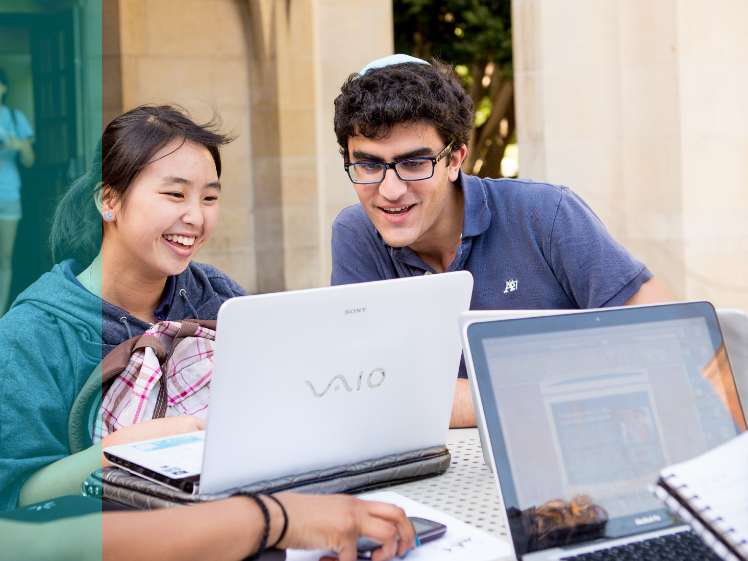 Several students study and have fun at an outdoor table.
