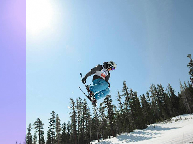 A competitive skier grabs one of her skis in a jump high above the slope.