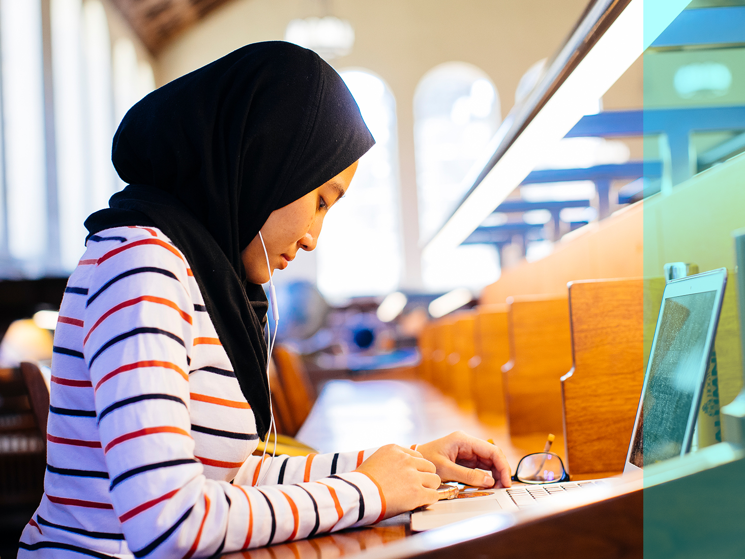 A woman wearing a headscarf does research on a computer in the library.
