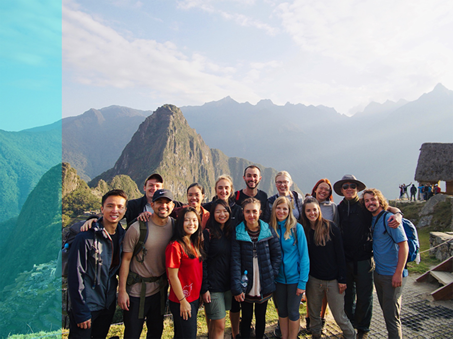 A group of study abroad students pose in front of a mountainous backdrop.