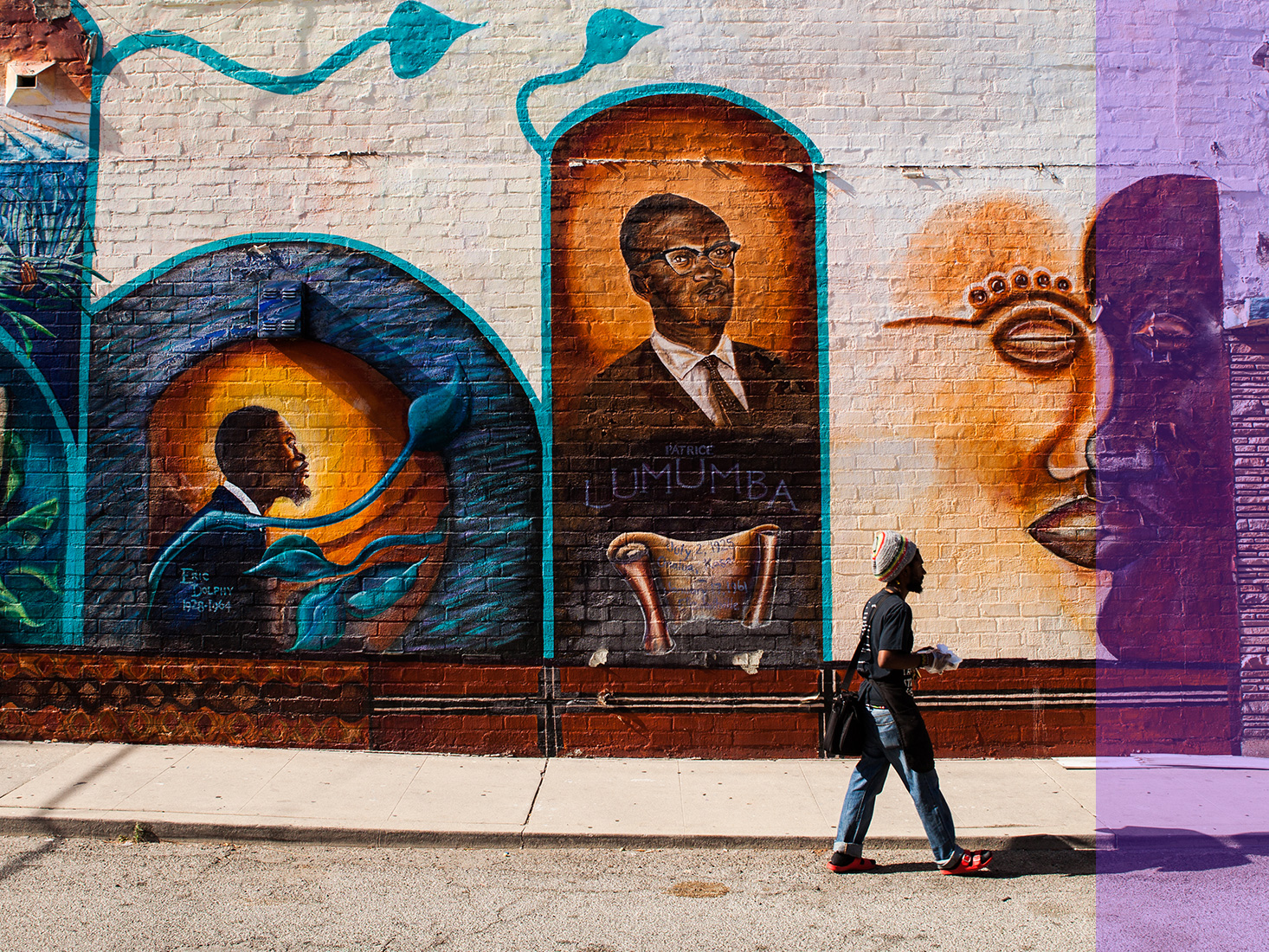 A woman walks by a large mural in the Liemert Park Village section of L.A.