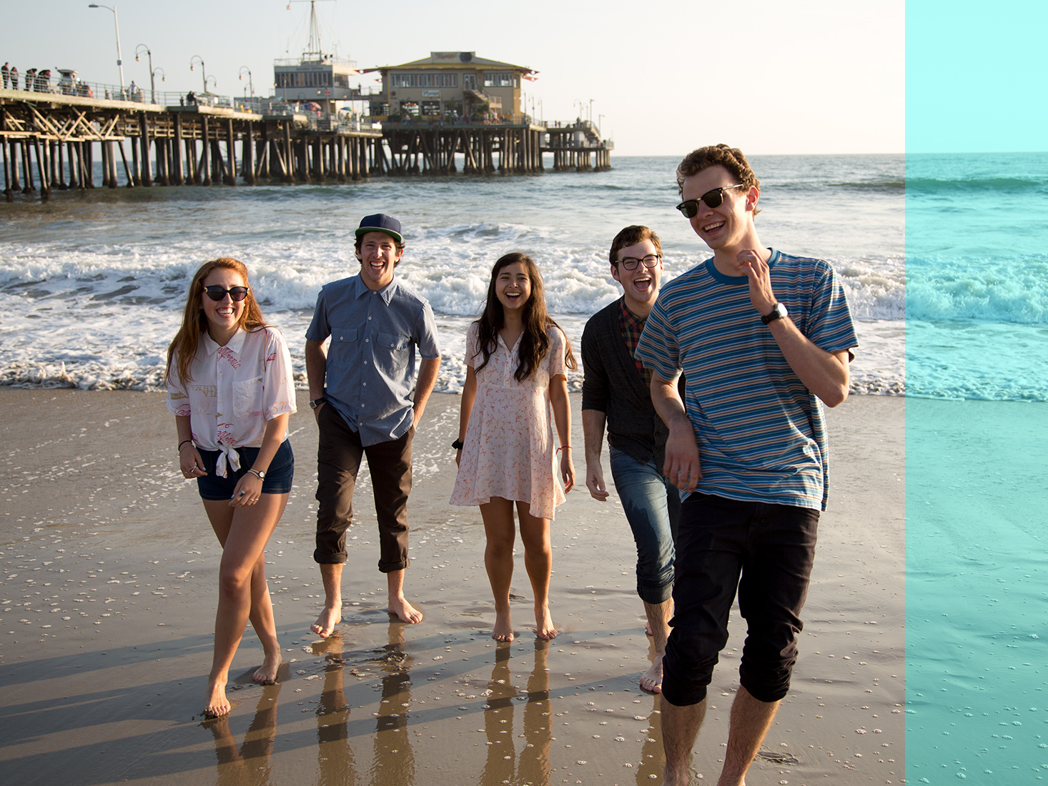 A group of students goof around on the beach near the pier.
