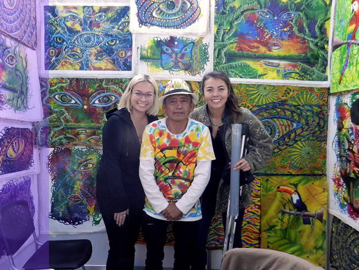 Two students pose with a local artist and his work in Peru.