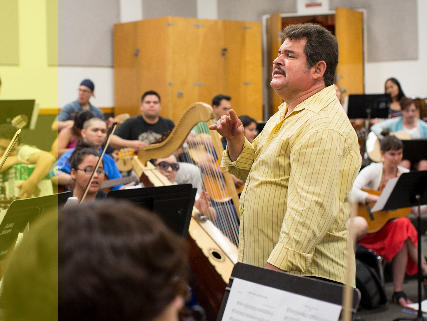 Arranger, director, instructor and musician Jesús Guzmán leads students in an orchestra.