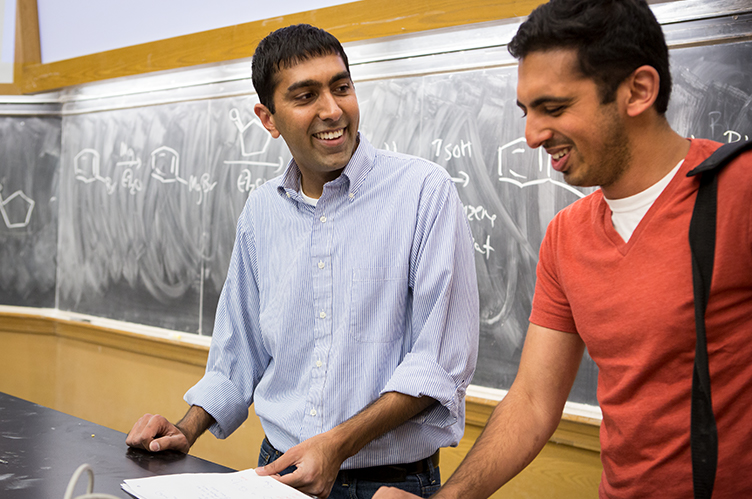 Professor Neil Garg shares a laugh with a student in his classroom.