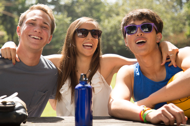 Three students enjoy each other's company at an outdoor table.