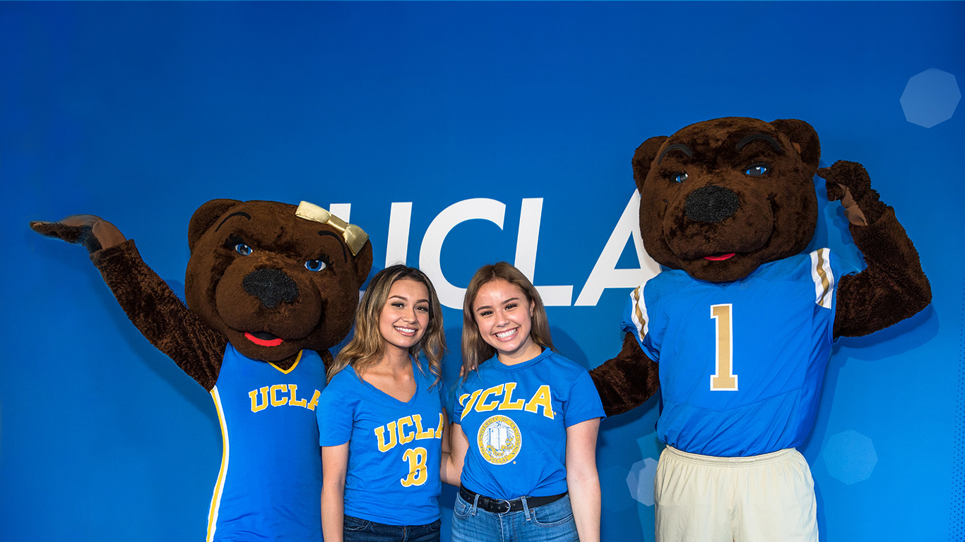 UCLA mascots Joe and Josie Bruin pose for a picture with two smiling students.