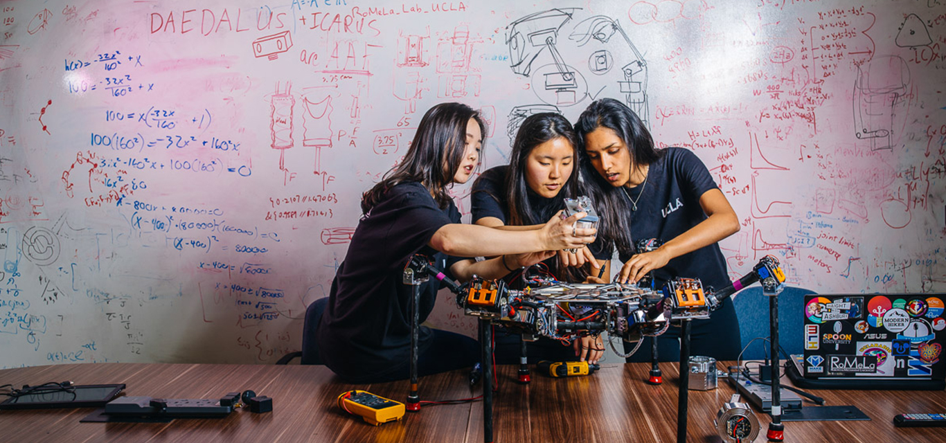Female students work together on a robotics project.