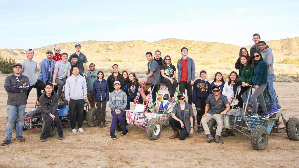 The Bruin Racing Baja SAE team poses with some off-road vehicles.