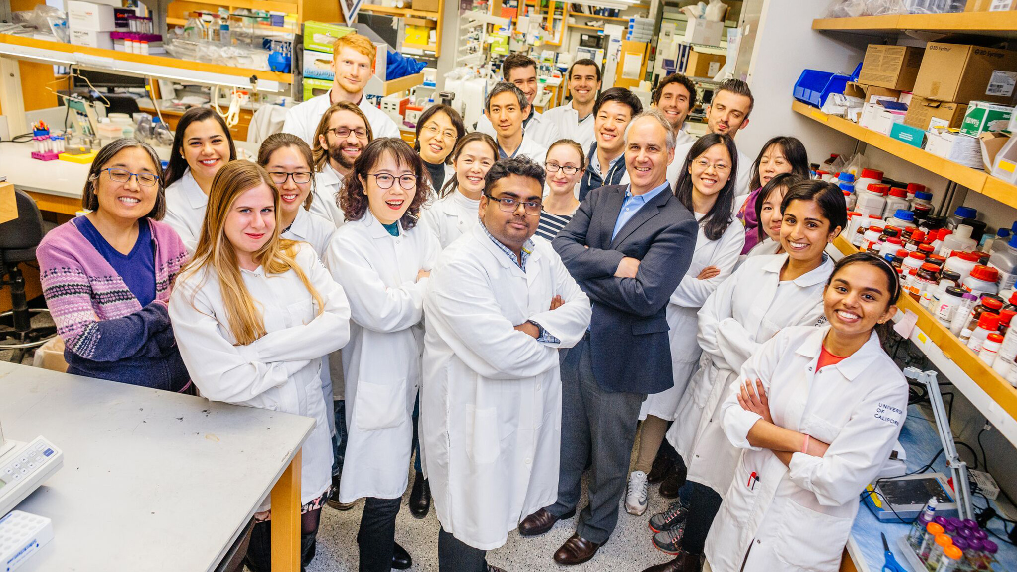 Professor Dan Geschwind smiles along with students in his lab.