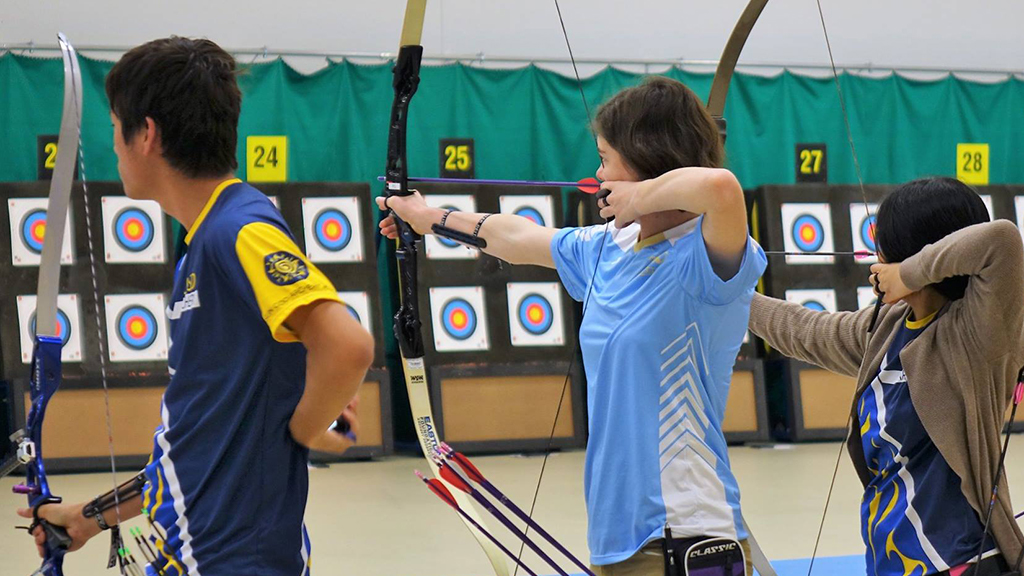 UCLA Archery members aim their bows and arrows at the bullseye.