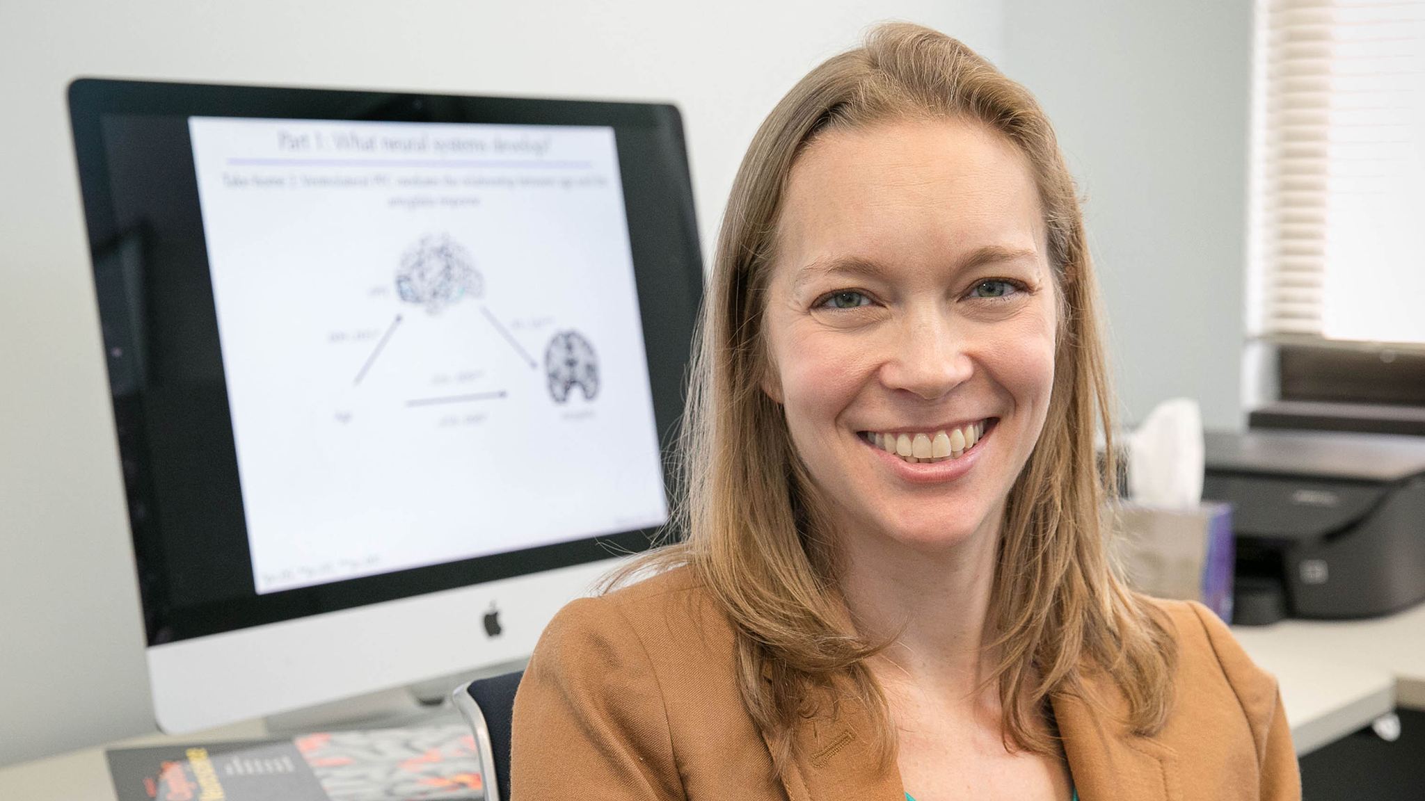 Assistant Professor of Psychology Jennifer Silvers pauses her computer research to smile for a photo.