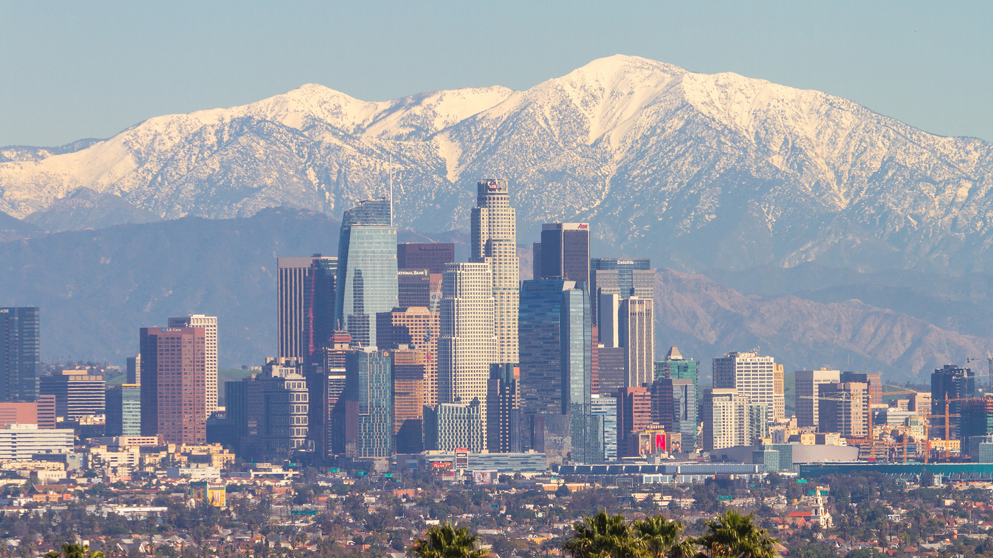 The San Gabriel mountains, seen in the distance behind downtown L.A., are topped with snow.