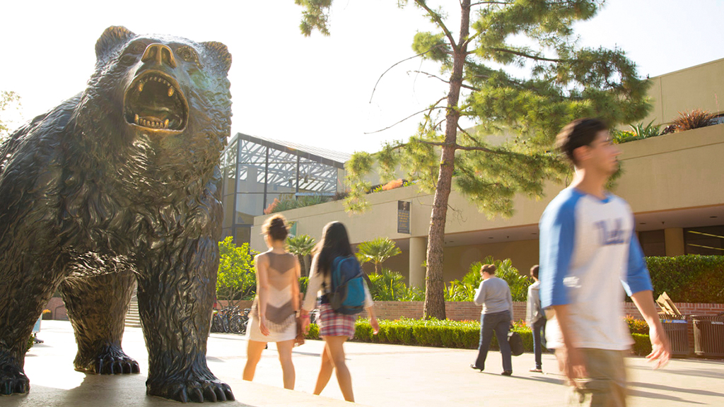 Students pass by The Bruin Statue and John Wooden Center.