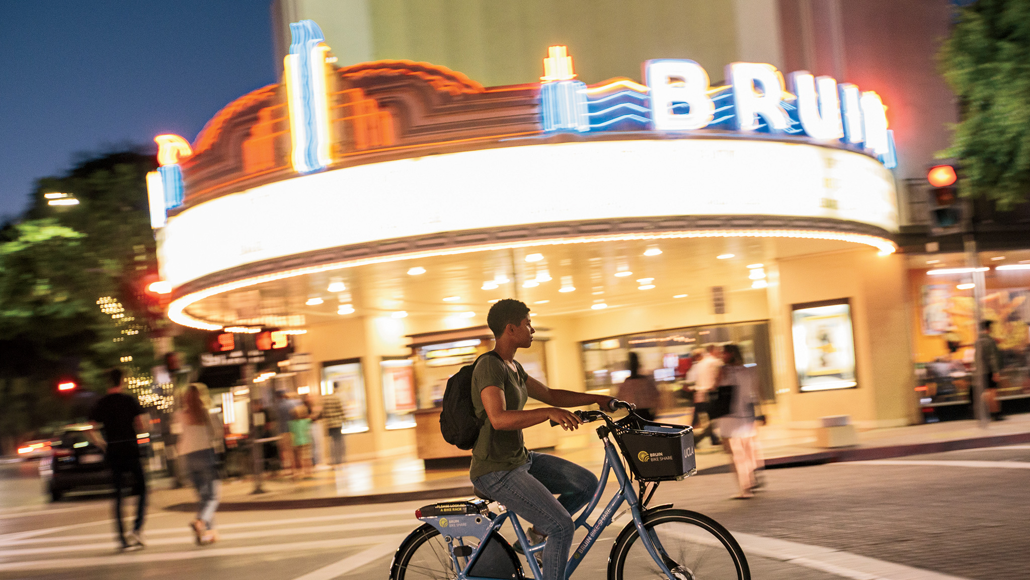A bike rider passes by the Bruin Theater in Westwood at night.
